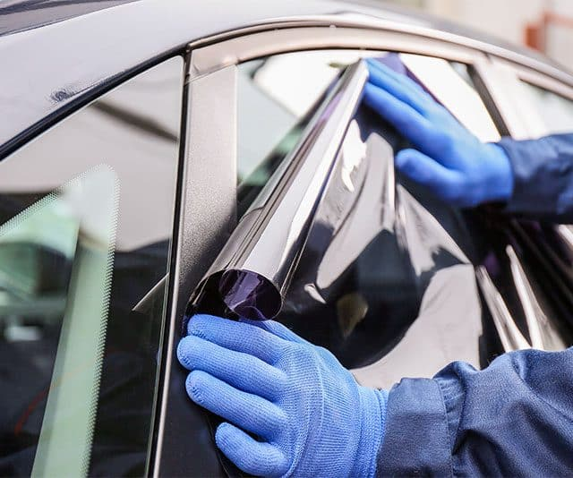 Closeup of professional removing window tint from a car
