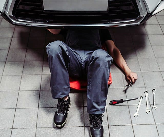 mechanic working on a car using an automotive creeper
